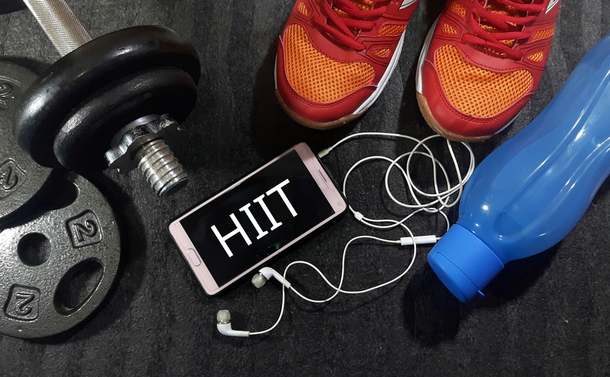 Healthy and fitness concept. Smartphone, dumbbell, water bottle and sport shoes on gym floor with word HIIT